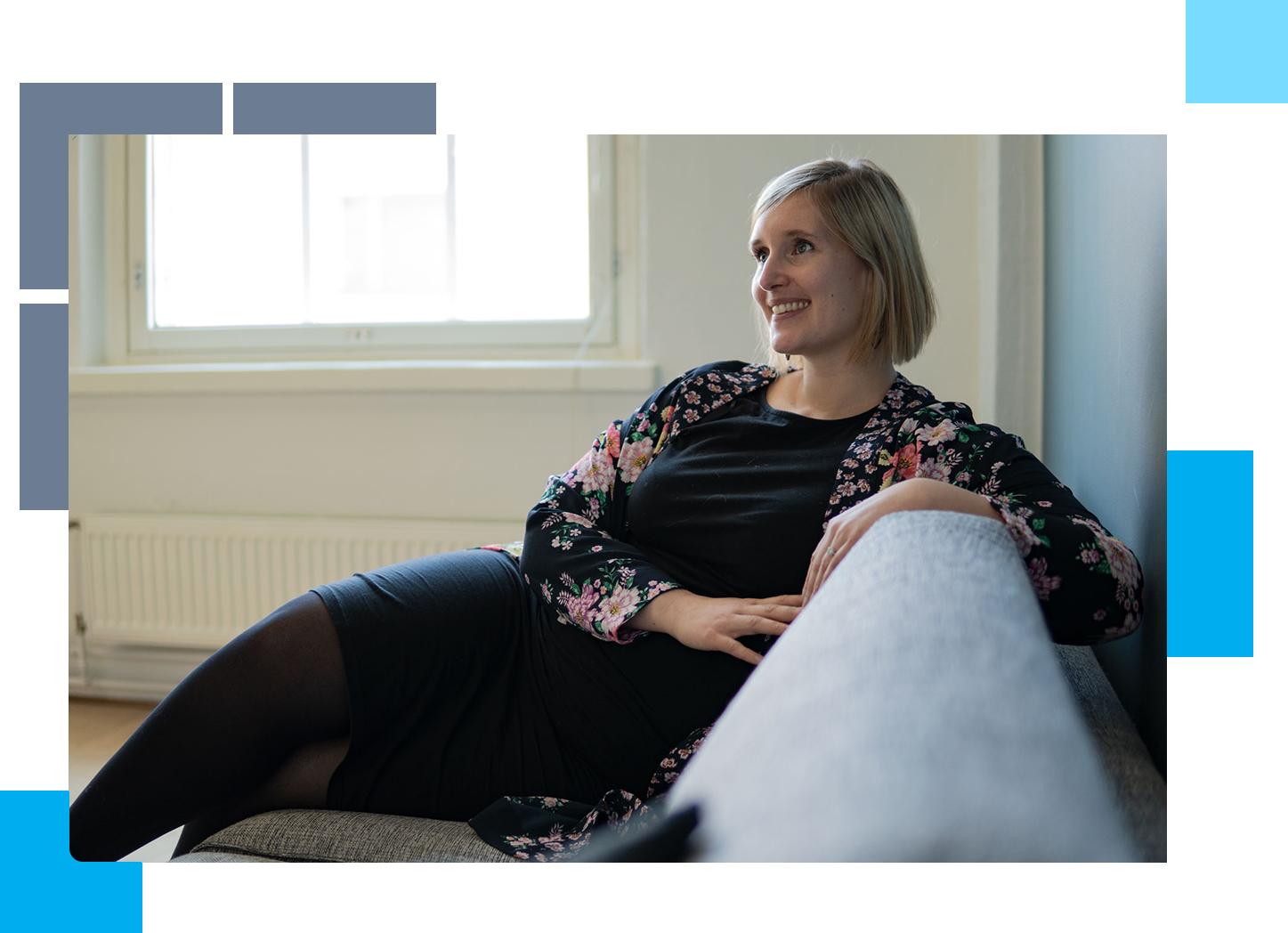 Jenni Reitti istumassa toimiston sohvalla