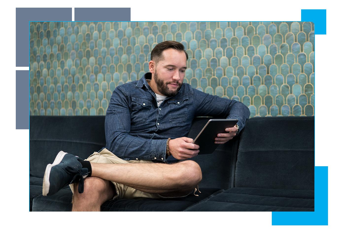 Timo Lausala istumassa toimiston sohvalla iPad kädessään